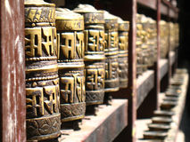 Row of Buddhist prayer wheels. In a temple, focus on the first wheel Royalty Free Stock Images