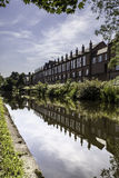Riverside buildings. A row of buildings reflected in the river on a sunny day Royalty Free Stock Photo