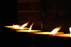 Row of burning candles. Row of burning tea light candles with black background stock photo