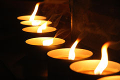 Row of burning candles. Row of burning tea light candles with dark background Stock Photo
