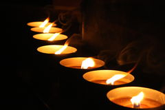 Row of burning candles. Row of burning tea light candles with black background stock photos