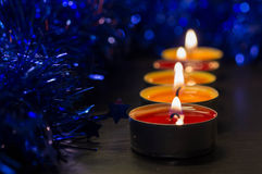 A row from burning candles and a Christmas decor Stock Image