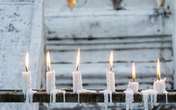 Row of burning candles with white temple wall as background Royalty Free Stock Photos