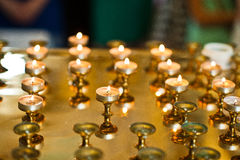 Row of burning circle candles on a golden stand at church Royalty Free Stock Photography
