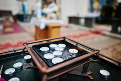 Row of burning circle candles on a stand at church Royalty Free Stock Photos