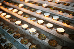 Row of burning circle candles on a stand at church Royalty Free Stock Photo
