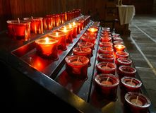 Burning white candles in red glasses in church royalty free stock photography