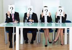 Row of businesspeople with question marks Stock Image