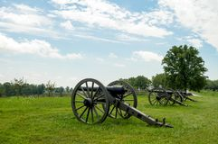 Row of Cannon Artillery Pointing over Landscape Stock Photography