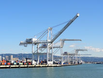 Row of Cargo Cranes tower over shoreline in Oakland Harbor on a Royalty Free Stock Images