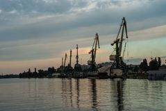 Cherkasy, Ukraine - June 01, 2013: Riverport. Port cranes. Row of cargo port cranes against the background of the evening sky. Cherkasy, Ukraine Royalty Free Stock Image