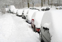 Row of cars covered in snow. Winter scene containing a sidewalk and cars parking in a row on the street, all covered in snow Stock Images