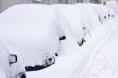 Row of cars covered in snow in a parking lot. Horizontal side view of a row of cars covered completely  in a city parking lot, winter time Stock Photos