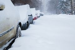 Row of cars covered with snow. Snowstorm. Row of cars covered with snow in the yard. Snowstorm Royalty Free Stock Photography