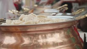 The row of casseroles with pelmeni, rice and other asian food. Pelmeni on foreground are focused.