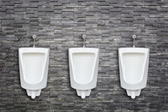 Row of ceramic outdoor urinals in men public toilet install on t Royalty Free Stock Photos