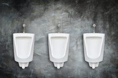 Row of ceramic outdoor urinals in men public toilet install on t. New row of ceramic outdoor urinals in men public toilet install on the wall Stock Photo
