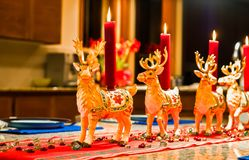 Reindeer Christmas Decorations. Row of ceramic reindeer figurine candle holders with lit red candles on home kitchen counter. Shallow depth of field stock photos