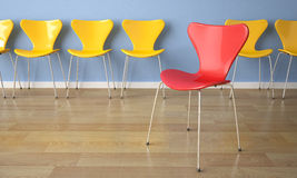 Row of chairs on blue wall stock illustration