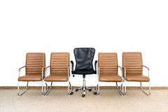 Row of chairs with one different chair in the middle. Job opportunity. Business leadership or recruitment concept. Search the best person from a group of Royalty Free Stock Images