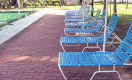 A row of chairs series 1. A row of benches by the poolside in a resort Royalty Free Stock Photography
