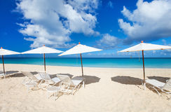 Chairs and umbrellas on tropical beach. Row of chairs and umbrellas on a beautiful tropical beach at Anguilla, Caribbean Stock Photography