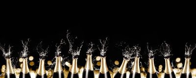 Sparkling wine bottles panorama. A row of champagne bottles with splashing liquid Stock Photos