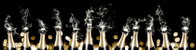 Foaming and splashing champagne bottles banner. A row of 12 champagne bottles sputtering with liquid and foam in front of a black background with golden bokeh Royalty Free Stock Photo