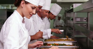 Row of chefs preparing food in serving trays. In a commercial kitchen stock video footage