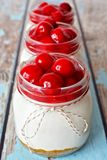 Row of cherry cheesecakes in mason jars Stock Photography