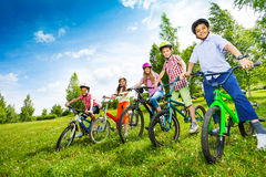 Row of children in colorful helmets holding bikes Stock Photo