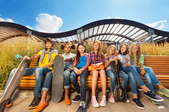 Row of children together on bench hold skateboards Royalty Free Stock Photos