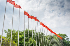 A row of Chinese National flag being hoisted up the flagpole against cloudy sky in the park. During Chinese holidays Stock Photos