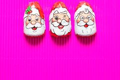 A row of chocolate covered with Santa Claus face wrappers Royalty Free Stock Photos