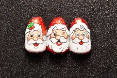 A row of chocolate covered with Santa Clauses face wrappers Stock Photo