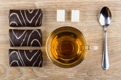 Row of chocolate swiss rolls, tea, lumpy sugar, teaspoon Royalty Free Stock Image