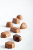 Row of Chocolates. On a white background with a shallow depth of field Royalty Free Stock Photography