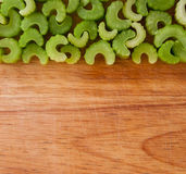 Row of chopped celery pieces against wood Royalty Free Stock Photography
