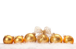 Row of Christmas balls. A row of gold Christmas balls in fur on white background Royalty Free Stock Photography