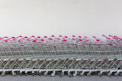Row of chrome shopping carts. At supermarket against white wall Royalty Free Stock Image