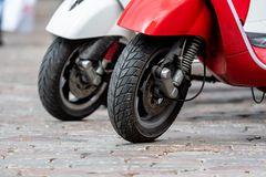 Row of classic scooter parking by street.  Closeup of a front wheel - image royalty free stock photography