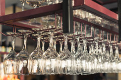 A row of clean empty wine glasses hang Stock Photo