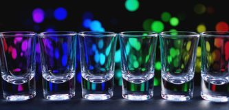 Row of clean shiny glasses on a bar counter in a nightclub ready for barmen. Row of clean shiny glasses lined up on a bar counter in a nightclub ready for the stock photography