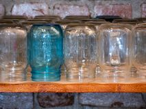 Row of storage jars on shelf against brick wall stock images