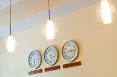 Row of clocks showing different time and lamps. Row of clocks hanging on wall Royalty Free Stock Photos