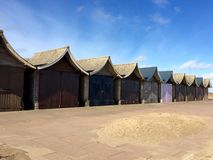 A row of closed beach huts on a sandy promenade. A row of closed curved roof beach huts on a sandy sea front royalty free stock images