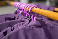 Row of cloth hangers with coats. Row of cloth hangers with purple coats Royalty Free Stock Photography