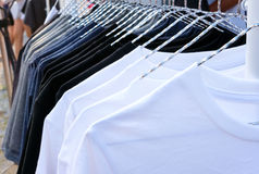 Row of cloth hangers. With shirts in the market Royalty Free Stock Photo