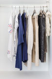 Row of cloth hanging on coat hanger. In wardrobe Royalty Free Stock Image