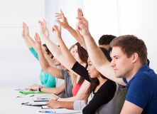 Row of college students raising hands Stock Photo